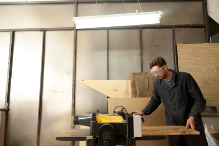 Carpenter trims massive wooden board on woodworking thickness planer machine. Joiner working at own small sawn timber manufacture. Young entrepreneur developing his local sawmill, furniture business Фото со стока