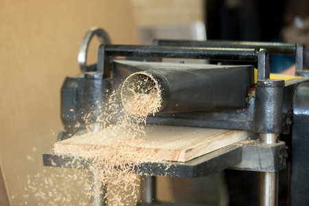 Woodworking industry and wood processing. Stationary power planer smoothing surface of a wooden plank with lot of sawdust, furniture, floor, window frame manufacture, construction materials, close up Reklamní fotografie