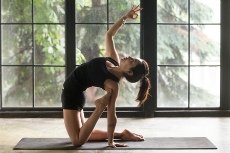 Young attractive woman practicing yoga at home, stretching in Ustrasana exercise, Camel pose with mudra, working out, wearing sportswear, black shorts and top, indoor full length, window background Stock Photo