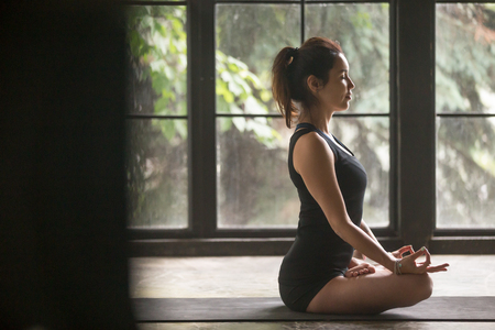 Young woman practicing yoga, sitting in Padmasana exercise, Lotus pose, mudra gesture, eyes closed, working out, wearing sportswear, black shorts, top, indoor full length, home studio life style photo