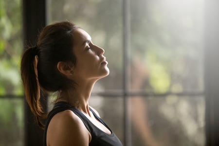 close up eyes: Profile portrait of young attractive yogi woman breathing fresh air, her eyes closed, meditation pose, relaxation exercise, working out wearing black sportswear top, close up image, window background