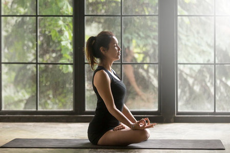 Young attractive woman practicing yoga, sitting in Padmasana exercise, Lotus pose, mudra gesture, eyes closed, working out, wearing sportswear, black shorts, top, indoor full length, window background Stock Photo