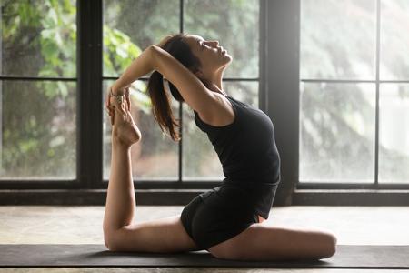 Giovane donna pratica dello yoga, che si estende nell'esercizio One Legged King Pigeon, posa di Eka Pada Rajakapotasana, lavorando, indossando abbigliamento sportivo, pantaloncini neri e top, coperta tutta la lunghezza, sfondo di casa Archivio Fotografico