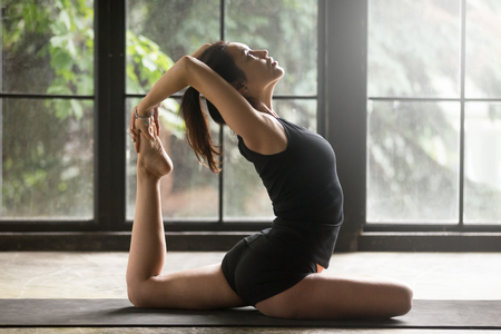 Young woman practicing yoga, stretching in One Legged King Pigeon exercise, Eka Pada Rajakapotasana pose, working out, wearing sportswear, black shorts and top, indoor full length, home background Imagens
