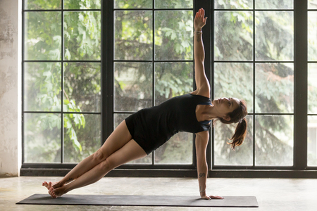 Young attractive woman practicing yoga at home, standing in Side Plank exercise, Vasisthasana pose, yogi model working out, wearing sportswear, black shorts, top, indoor full length, studio background Stock Photo