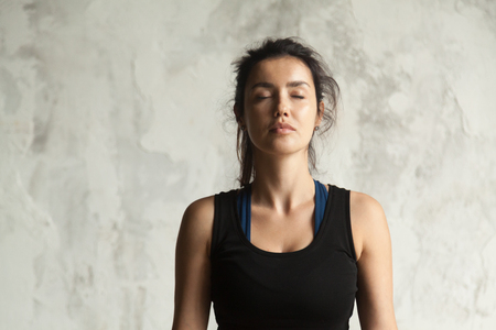 Portrait of young attractive yogi woman with her eyes closed in meditating pose, relaxation exercise, working out, wearing sportswear, black top, indoor close up image, wall background