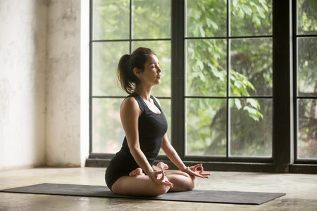 Young woman with tattoo practicing yoga, sitting in Padmasana exercise, Lotus pose, mudra gesture, eyes closed, working out, wearing sportswear black shorts and top, indoor full length, studio or home