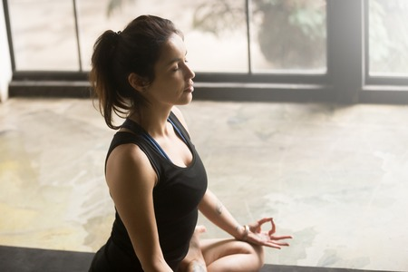 close up eyes: Young woman with tattoo practicing yoga, sitting in Padmasana exercise, Lotus pose, mudra gesture, her eyes closed, working out, wearing sportswear, black top, indoor close up photo, studio or home