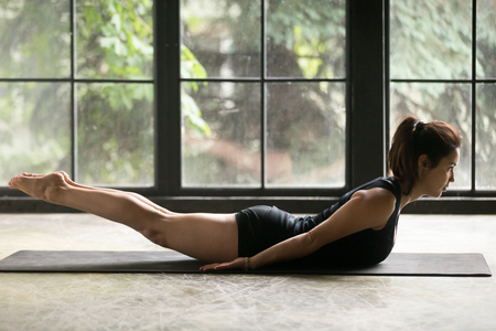 Young attractive woman practicing yoga at home, stretching in Salabhasana exercise, Double Leg Kicks pose, working out, wearing sportswear, black shorts and top, indoor full length, studio background