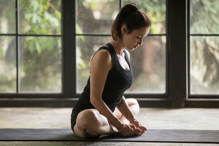 Young attractive woman practicing yoga at home, sitting in Butterfly exercise, baddha konasana pose, working out, wearing sportswear, black shorts and top, indoor full length, studio background Stock Photo