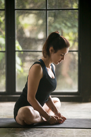 Young attractive woman practicing yoga at home, sitting in Butterfly exercise, baddha konasana pose, working out, wearing sportswear, black shorts and top, indoor full length, window background