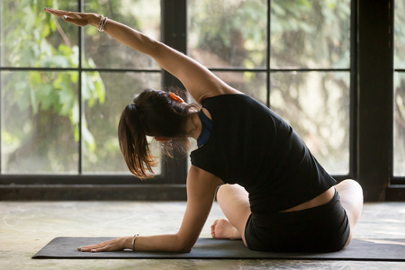 Young sporty woman practicing yoga at home, doing Side bending exercise, Sukhasana pose, model working out, wearing sportswear, black shorts and top, indoor full length, window background, rear view Stok Fotoğraf