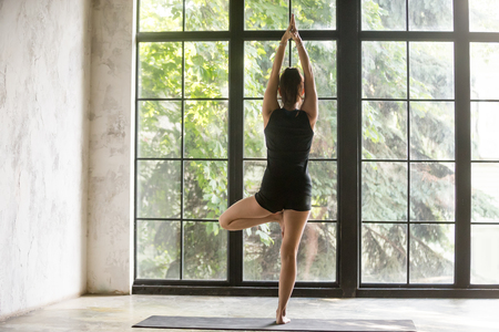 Young sporty woman practicing yoga at home, standing in Vrksasana exercise, Tree pose, working out, wearing sportswear, black shorts and top, indoor full length, studio background, rear view