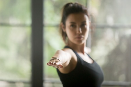 Young attractive woman practicing yoga at home, standing in Warrior Two exercise, Virabhadrasana II pose, working out wearing sportswear black top, indoor close up, studio background, focus on fingers