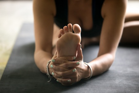 Close up sole image, woman practicing yoga at home, sitting in Janu Sirsasana exercise, Head to Knee Forward Bend pose, working out, wearing sportswear, black top, mat background. Wellness concept