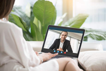 Young woman sitting on sofa communicates with man in formal suit via video call application. Couple chatting. Long distance relationship, virtual communication concept. Close up view, focus on screen. Stockfoto