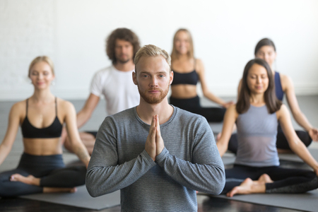 Group of young sporty people practicing yoga lesson with instructor, sitting in Sukhasana exercise, Easy Seat pose, friends working out in club, focus on male student, making mudra gesture, studio Foto de archivo