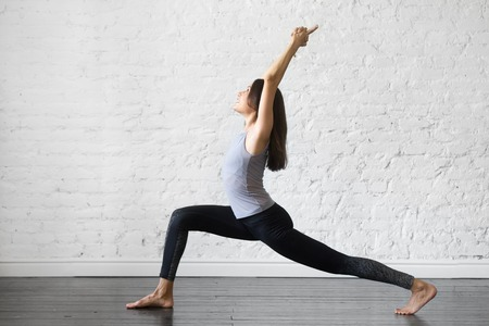 Young attractive woman practicing yoga, standing in Warrior one exercise, Virabhadrasana I pose, working out, wearing sportswear, gray tank top, black pants, indoor full length, studio background