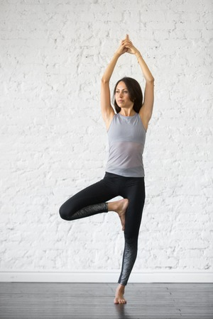 Young attractive woman practicing yoga, standing in Vrksasana exercise, Tree pose, working out, wearing sportswear, gray tank top, black pants, indoor full length, studio background Stock Photo - 87651189