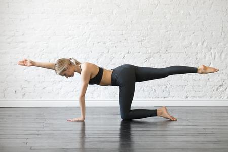 Giovane donna attraente, praticando yoga, stretching in esercizio di cane uccello, posa di asino calcio, lavorando, indossando abbigliamento sportivo, top nero e pantaloni, coperta tutta la lunghezza, sfondo di studio Archivio Fotografico - 87527948