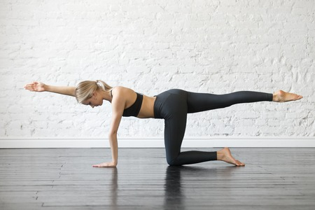 Young attractive woman practicing yoga, stretching in Bird dog exercise, Donkey kick pose, working out, wearing sportswear, black top and pants, indoor full length, studio background 版權商用圖片
