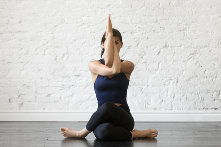 Young attractive woman practicing yoga, sitting in Gomukasana exercise, Cow Face pose, working out, wearing sportswear, black top and pants, indoor full length, studio background Archivio Fotografico