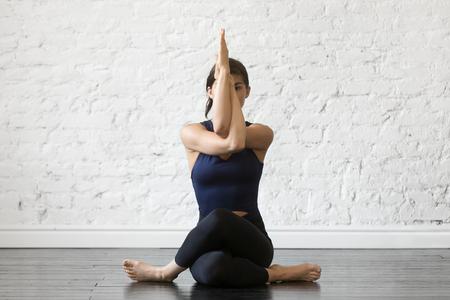 Mujer atractiva joven practicando yoga, sentado en el ejercicio Gomukasana, postura de la cara de vaca, trabajando, vistiendo ropa deportiva, top negro y pantalones, interior de cuerpo entero, fondo de estudio