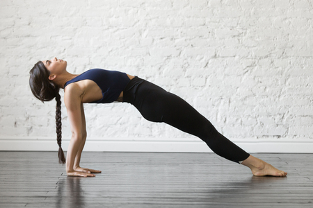 Young attractive woman practicing yoga, stretching in Purvottanasana exercise, Upward Plank pose, working out, wearing sportswear, black top and pants, indoor full length, studio background Stock fotó