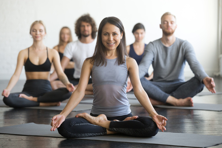 Group of young sporty people practicing yoga lesson with instructor, sitting in Sukhasana exercise, Easy Seat pose, friends working out in club, focus on woman in Padmasana, indoor full length, studio 版權商用圖片
