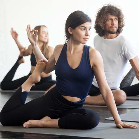 Group of young sporty attractive female and male students working out, practicing yoga lesson with instructor, sitting in Mermaid exercise, Eka Pada Rajakapotasana pose. Wellbeing, wellness concept Stock Photo