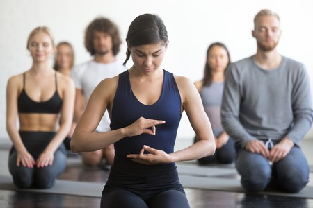 Group of young sporty people practicing yoga lesson with instructor, sitting in vajrasana exercise, seiza pose, working out, indoor, studio. Wellbeing, wellness concept. Portrait of yogi teacher