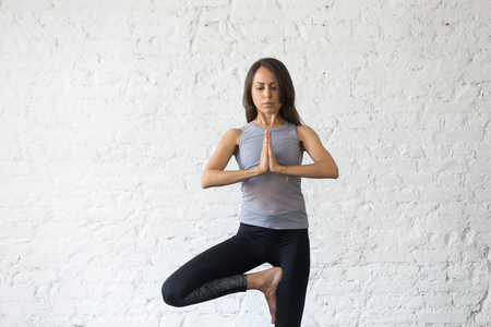Young attractive woman practicing yoga, standing in Vrksasana exercise, Tree pose with mudra, working out, wearing sportswear, gray tank top, black pants, indoor close up image, studio background