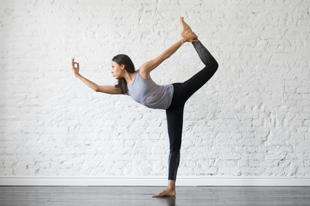 Young attractive woman practicing yoga, stretching in Natarajasana exercise, Lord of the Dance pose, working out, wearing sportswear, gray tank top, black pants, indoor full length, studio background Stock Photo