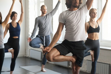Group of young sporty people practicing yoga lesson with instructor, standing in Vrksasana exercise, Tree pose, working out, indoor close up image length, studio. Wellbeing, wellness concept