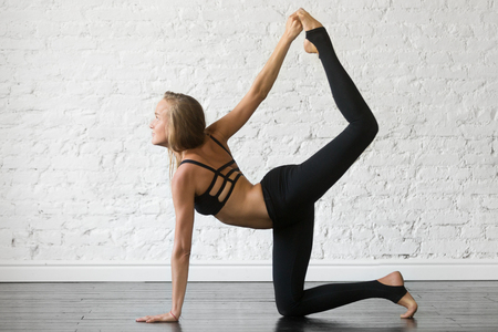 Young attractive woman practicing yoga, stretching in Bird dog exercise, tiger pose, working out, wearing sportswear, black top and pants, indoor full length, studio background