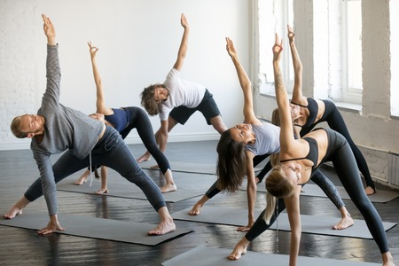 Group of young sporty people practicing yoga lesson with instructor, standing in Trikonasana exercise, extended triangle pose, working out indoor, full length studio. Wellbeing, wellness concept