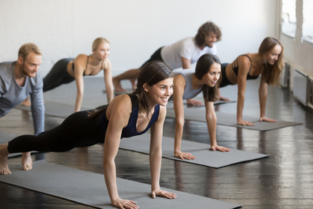 Group of young sporty attractive people practicing yoga lesson with instructor, doing Push ups or press ups exercise, standing in Plank pose, friends working out in club, indoor full length, studio