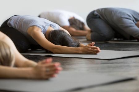 Gruppe junge sportliche Leute, die Yogastunde mit dem Lehrer üben, sitzend in Balasana-Übung, Kinderhaltung, Freunde, die im Verein, Innennahes hohes Bild, Studio ausarbeiten. Wohlbefinden, Wellness-Konzept