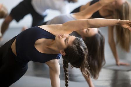 Groep jonge sportieve mensen die yogales met instructeur uitoefenen, die zich in het Buigen van Zijplankoefening, Vasisthasana uitrekken, het uitwerken, binnen dicht omhooggaand beeld, studio, glimlachende vrouw in nadruk