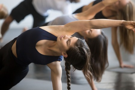 Group of young sporty people practicing yoga lesson with instructor, stretching in Bending Side Plank exercise, Vasisthasana pose, working out, indoor close up image, studio, smiling woman in focus Banco de Imagens - 87651221