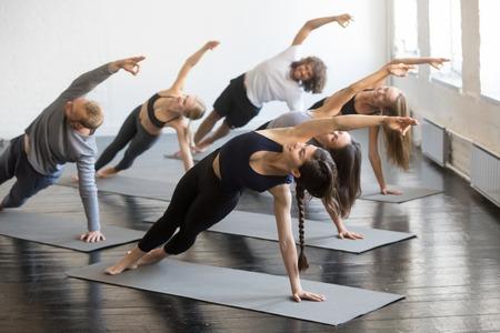 Grupo de jovens pessoas desportivas que praticam aula de ioga com o instrutor, esticando no exercício Bending Side Plank, pose de Vasisthasana, trabalhando, imagem de estúdio coberta. Bem-estar, conceito de bem-estar Foto de archivo