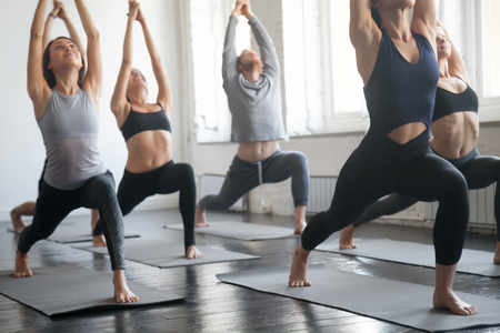 Group of young sporty attractive people practicing yoga lesson with instructor, standing together in Virabhadrasana 1 exercise, Warrior one pose, working out, full length, studio background, close up