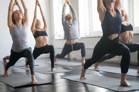 Grupo de jovens esportivos pessoas atraentes que praticam lição de ioga com instrutor, parados juntos em Virabhadrasana 1 exercício, Guerreiro uma pose, trabalhando, comprimento total, fundo do estúdio, close up