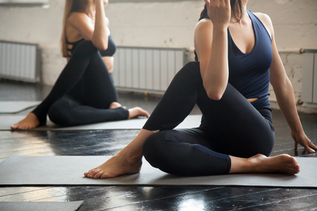Group of young sporty people practicing yoga lesson with instructor, sitting in Half lord of the fishes exercise, working out indoor, close up image, studio. Wellbeing, wellness concept