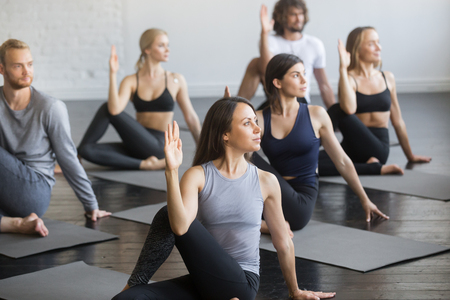 Group of young sporty people practicing yoga lesson with instructor, sitting in Half lord of the fishes exercise, Ardha Matsyendrasana pose, working out, indoor studio. Wellbeing, wellness concept Reklamní fotografie