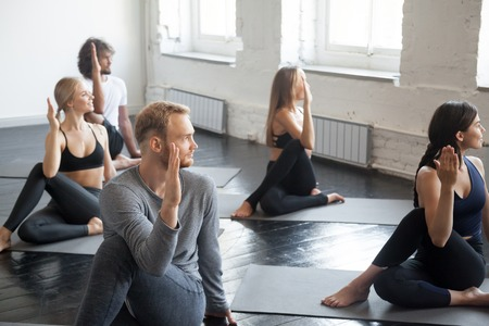 Group of young sporty people practicing yoga lesson with instructor, sitting in Half lord of the fishes exercise, Ardha Matsyendrasana pose, working out, indoor, studio. Wellbeing, wellness concept Reklamní fotografie