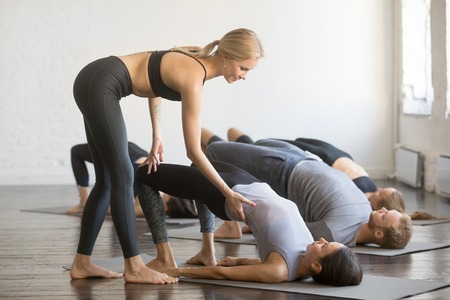 Group of young sporty people practicing yoga lesson with instructor, stretching, doing Glute Bridge exercise, female teacher correcting dvi pada pithasana pose, working out, indoor full length, studio Archivio Fotografico