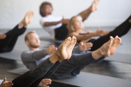 Grupo de jóvenes deportistas que practican la lección de yoga con el instructor, que se extiende en el ejercicio de Paripurna Navasana, pose del balance, resolviendo, imagen ascendente cercana, estudio, foco en pies