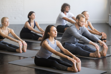Group of young sporty people practicing yoga lesson with instructor, sitting in paschimottanasana exercise, Seated forward bend pose, indoor full length, studio, friends working out in club