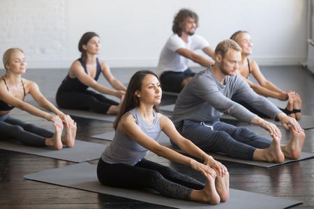 Gruppo di giovani sportivi che praticano la lezione di yoga con istruttore, seduto in esercizio paschimottanasana, posa di piega di andata messa, dell'interno pieno lunghezza, studio, amici che risolvono nel club Archivio Fotografico - 87651239